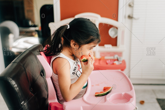 Girl in high chair eating water melon, side view