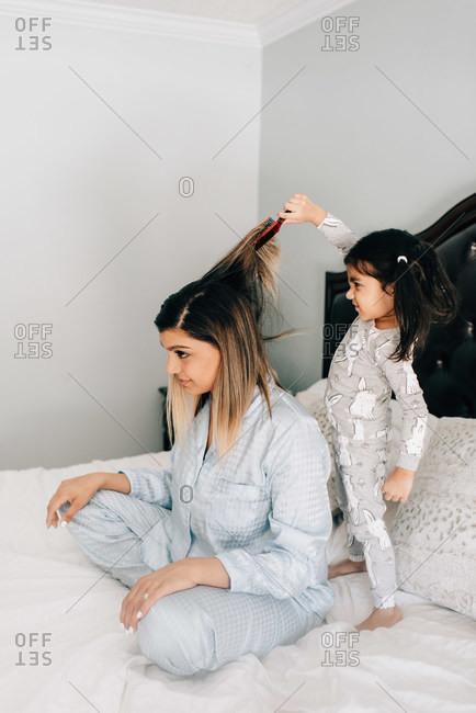 Girl brushing mother's hair on bed in morning