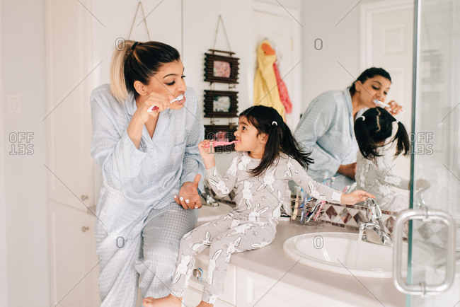 Girl and mother brushing their teeth in bathroom
