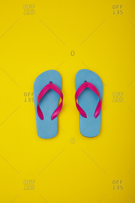 Pair of colorful flip-flops on sandy beach