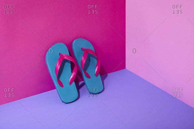 Pair of colorful flip-flops leaning on wall