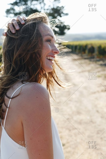 Woman laughing in sunshine in vineyard, Cape Town, South Africa
