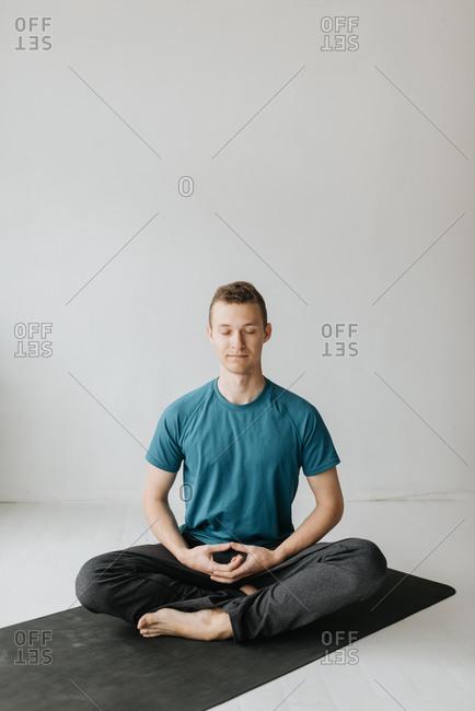 Man sitting in lotus pose in yoga studio
