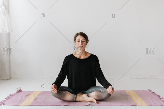 Woman sitting in lotus pose in yoga studio
