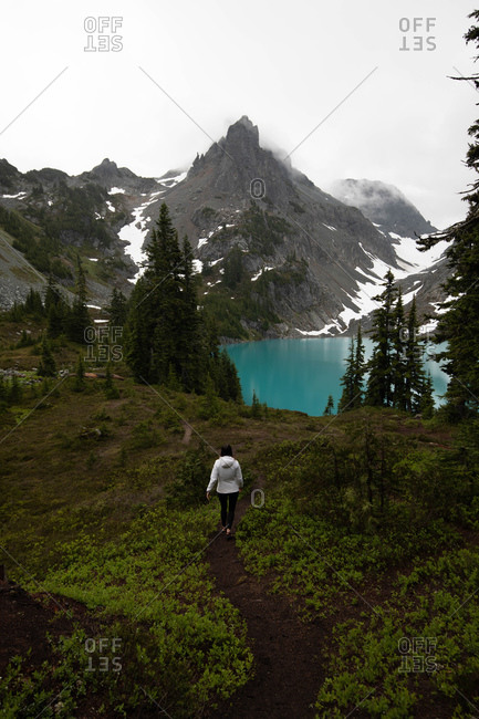 Tourist exploring wilderness, Alpine Blue Lake, Washington, USA