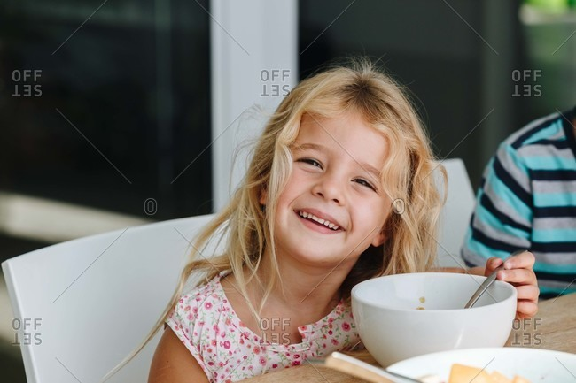 Happy little girl finishing lunch at home