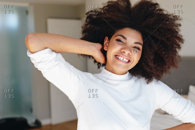Happy young woman with hand in afro hair in bedroom, head and shoulder portrait