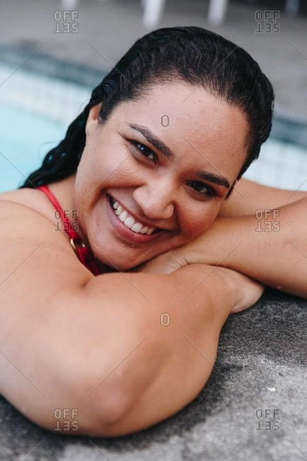 Mid adult woman with wet hair leaning on outdoor swimming poolside, head and shoulder portrait, Cape Town, South Africa