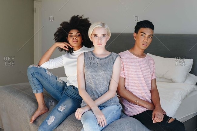 Cool mid adult man and two female friends sitting on bed, portrait