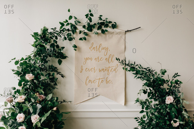 Romantic message on textile, hanging from floral foliage decoration at wedding reception