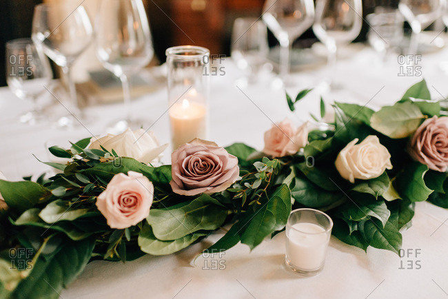 Place setting at wedding reception table with rose garland decoration, candles and drinking glasses