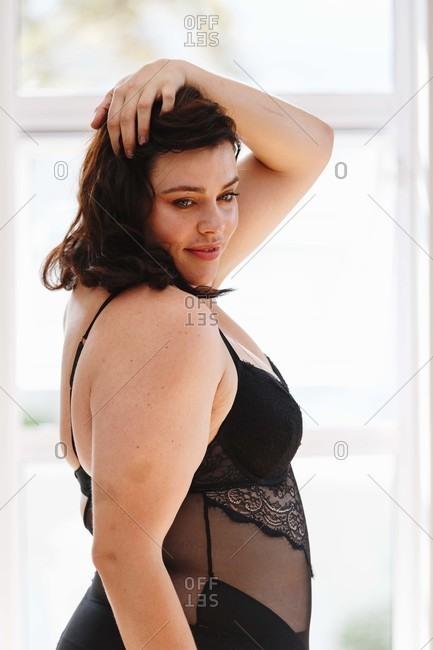 Woman in lingerie posing beside window