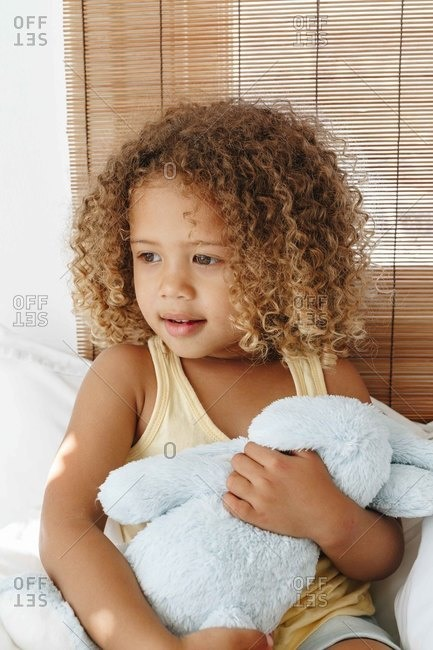 Little girl cradling soft toy, daydreaming in bed