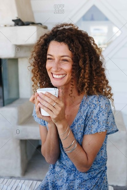 Woman enjoying hot drink clasped in hands at home