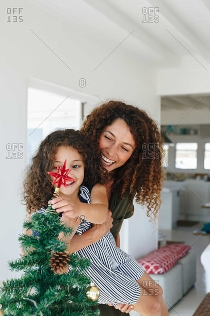 Mother helping daughter place star on Christmas tree at home