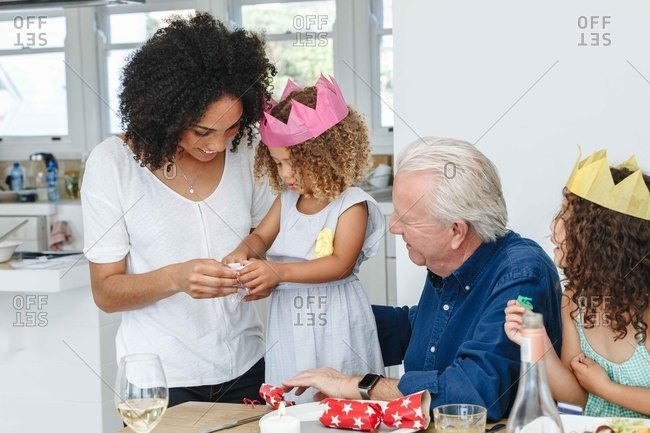 Woman teaching daughter fold paper flower at dining table