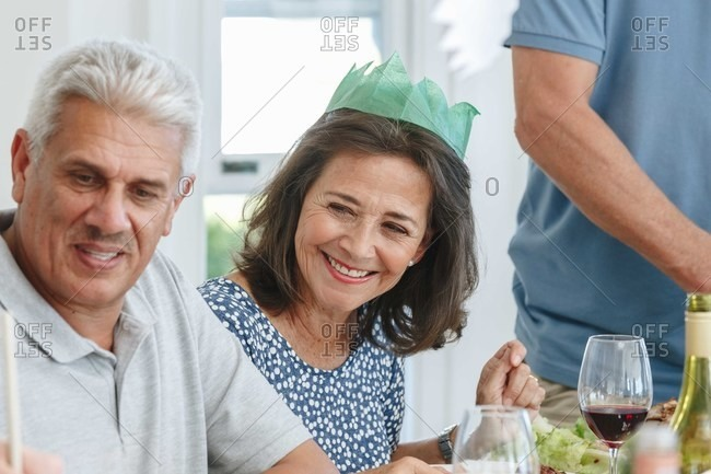 Senior couple listening attentively at dining table in home party