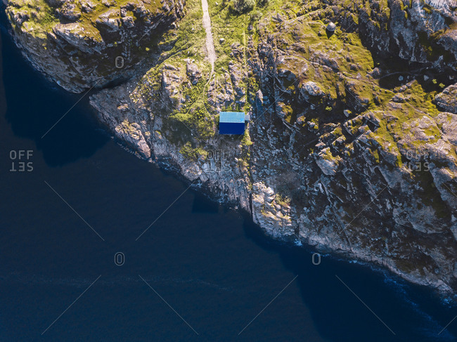 Aerial view of secluded hut standing on rocky shore of Barents Sea