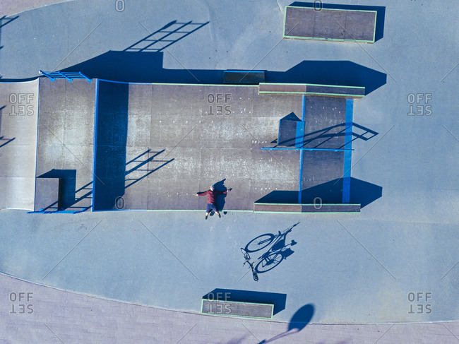 Man lying on concrete ramp in skate park- aerial view