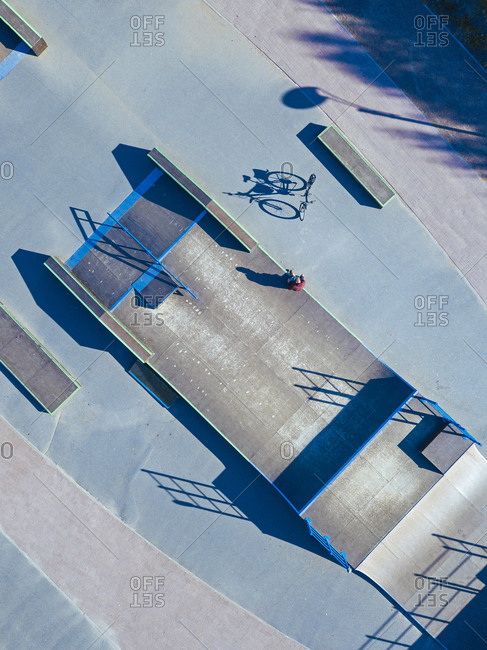 Man sitting on concrete ramp in skate park- aerial view
