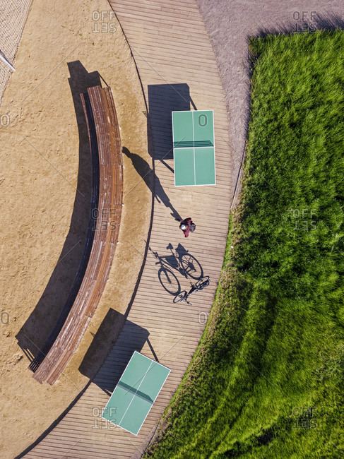Russia- Tikhvin- Man with bicycle on boardwalk with table tennis tables- aerial view