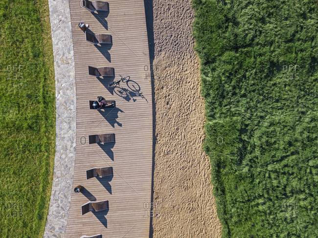 Russia- Tikhvin- Man with bicycle on boardwalk with sun loungers- aerial view