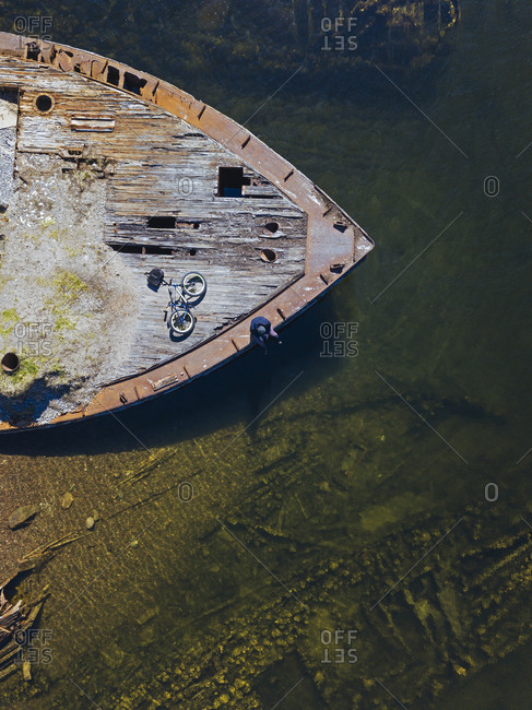Russia- Murmansk region- Kolsky District- Teriberka- Man with bicycle at old ship deck- aerial view