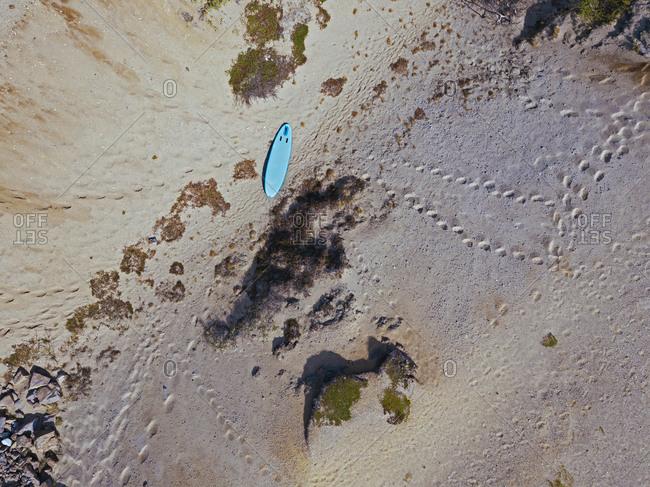 Blue surfboard on beach- aerial view