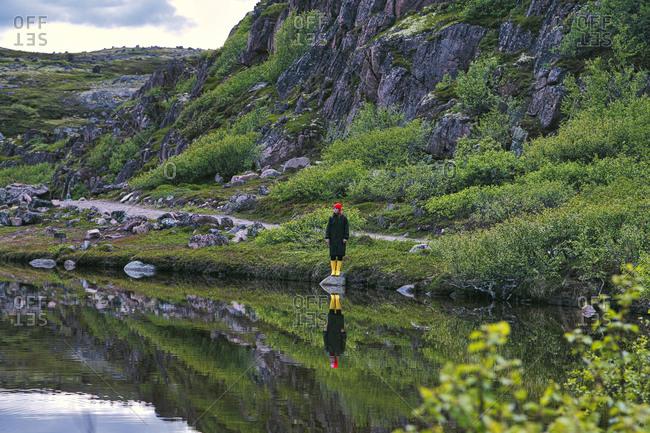 Woman standing on rock lakeshore- Teriberka- Murmansk Oblast- Russia