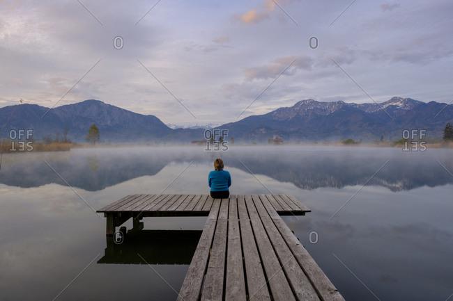 Germany- Bavaria- Schlehdorf- Woman sitting at end of jetty admiring Eichsee at foggy dawn