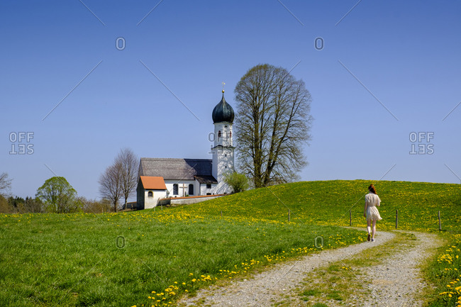 Germany- Bavaria- Bad Heilbrunn- Teenage girl walking along countryside dirt road toward Church of Saint Mary