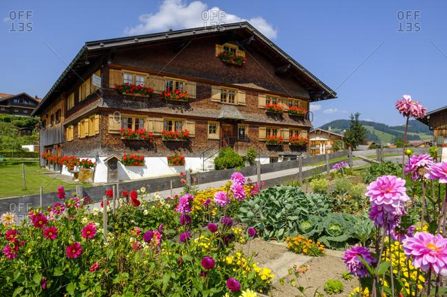 Germany- Bavaria- Swabia- Allgau- Oberstaufen- Flowers in garden and wooden rural house