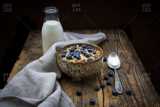 Milk bottle and bowl of granola with blueberries and quinoa