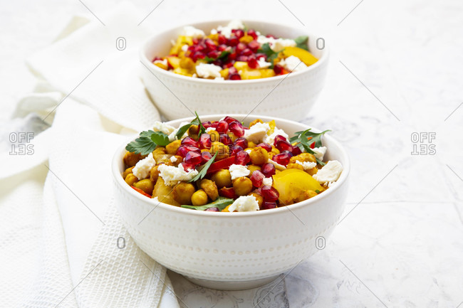 Two bowls of vegetarian salad with chick-peas- turmeric- bell peppers- tomatoes- parsley- feta cheese and pomegranate seeds