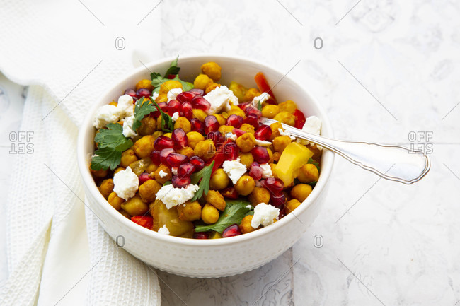 Bowl of vegetarian salad with chick-peas- turmeric- bell peppers- tomatoes- parsley- feta cheese and pomegranate seeds