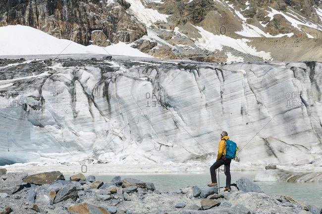Mature male hiker looking at melting glacier