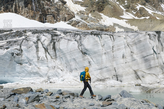 Male hiker exploring melting glacier while standing on rocks