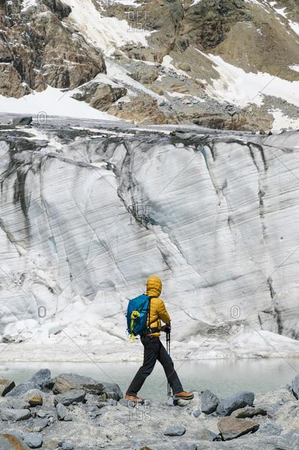 Mature man exploring melting glacier while standing on rocks