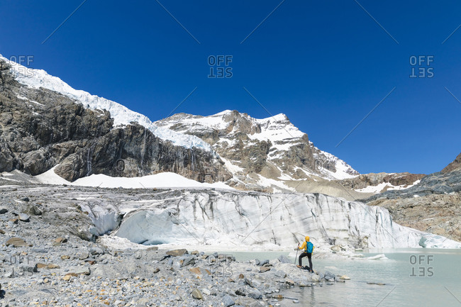 Mature man hiking while exploring snowcapped mountain against clear blue sky