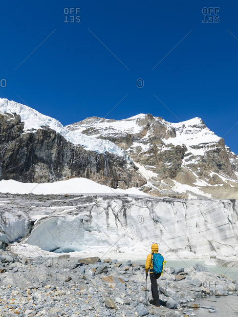 Man hiking while exploring snowcapped mountain against clear blue sky