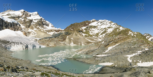 Panoramic view of glacier lagoon by mountain range against clear blue sky
