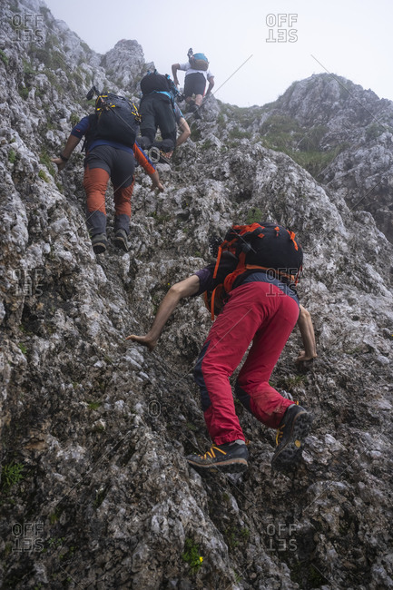 Male hikers with backpacks climbing on mountain- Bergamasque Alps- Germany