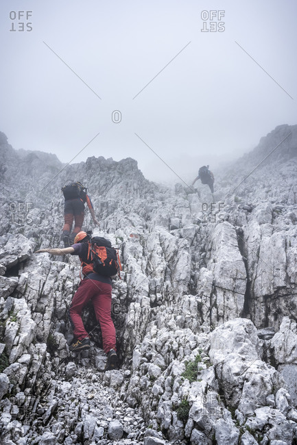 Male hikers climbing on rocky mountain against sky during foggy weather- Bergamasque Alps- Germany