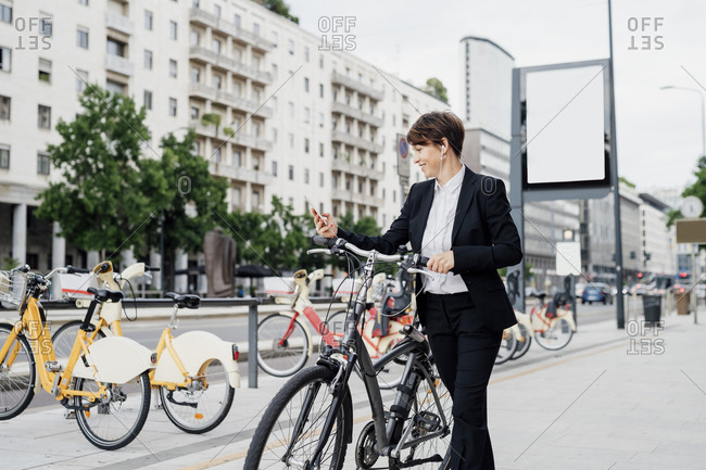 Businesswoman listening music while walking with bicycle on sidewalk in city
