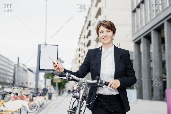 Female professional listening music while walking with bicycle on sidewalk in city