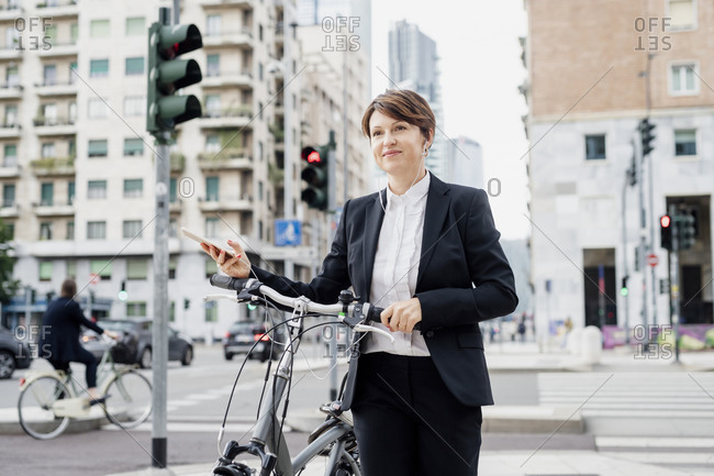 Female professional listening music while walking with bicycle on street in city