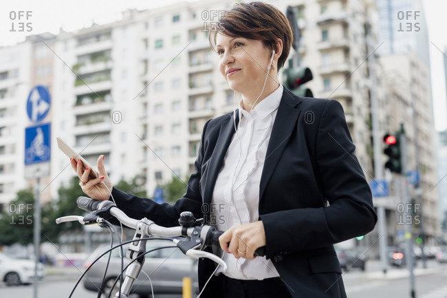 Female professional listening music while standing with bicycle in city
