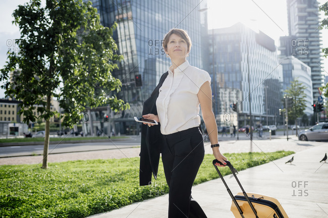 Confident businesswoman holding smart phone and suitcase while walking in city
