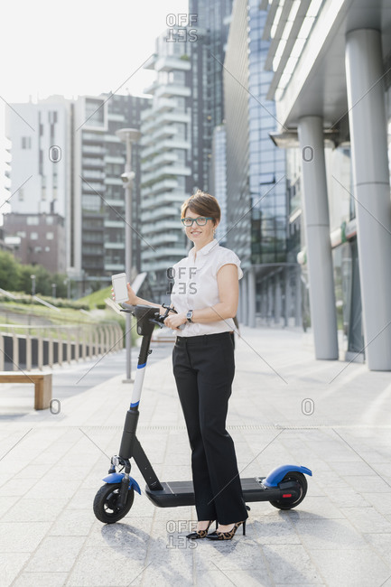 Businesswoman with electric push scooter standing on sidewalk in city