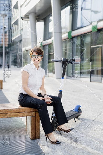 Smiling businesswoman with electric push scooter sitting on seat in city